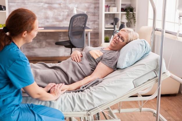 Vrouwelijke arts in verpleeghuis met hand van zieke oude vrouw.