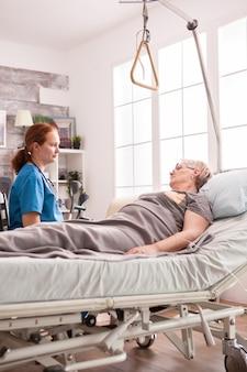 Vrouwelijke arts in verpleeghuis praten met senior vrouw met kanker.