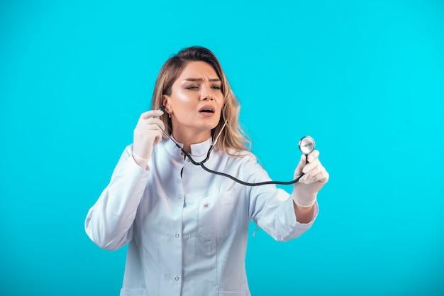 Vrouwelijke arts in wit uniform controleren met stethoscoop en aandachtig luisteren.