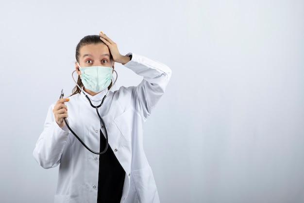 Vrouwelijke arts in wit uniform die een medisch masker draagt en een stethoscoop vasthoudt