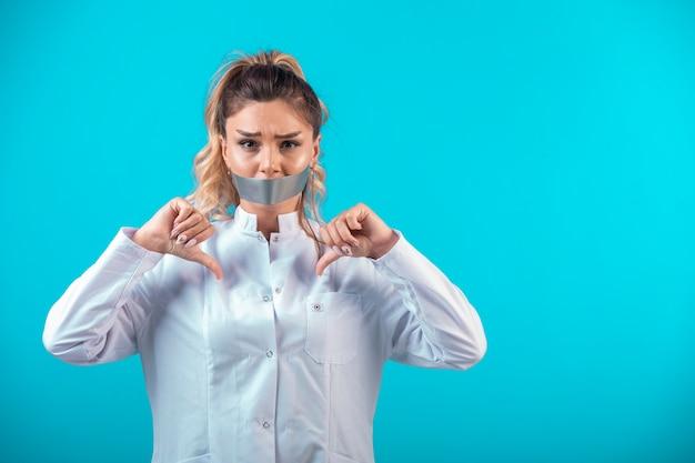 Vrouwelijke arts in wit uniform die haar mond bedekt en duimen naar beneden maakt.