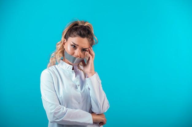 Vrouwelijke arts in wit uniform die haar mond bedekt.