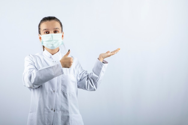 Vrouwelijke arts in wit uniform draagt een medisch masker met een duim omhoog