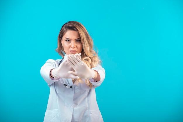 Vrouwelijke arts in wit uniform iets te voorkomen en te stoppen.