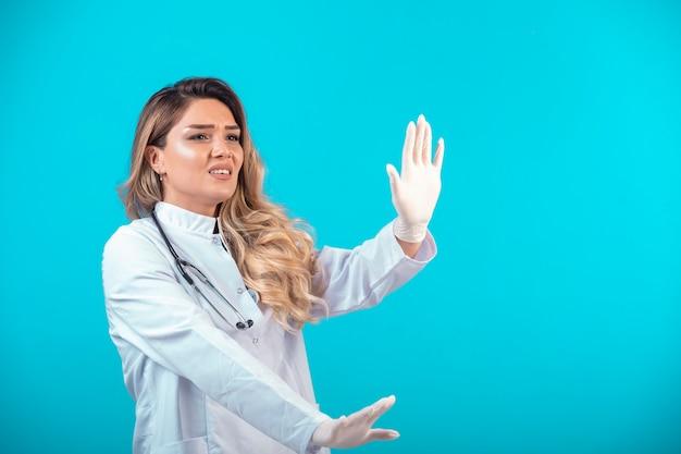 Vrouwelijke arts in wit uniform iets tegenhouden.