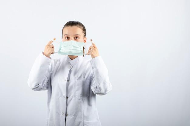 Vrouwelijke arts in wit uniform met een medisch masker