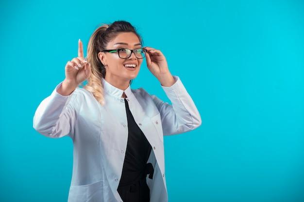 Vrouwelijke arts in wit uniform om aandacht te vragen.