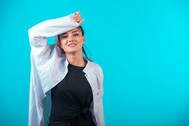 Vrouwelijke arts in wit uniform voelt zich moe.