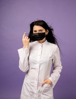 Vrouwelijke arts in witte jas en zwart masker op paars