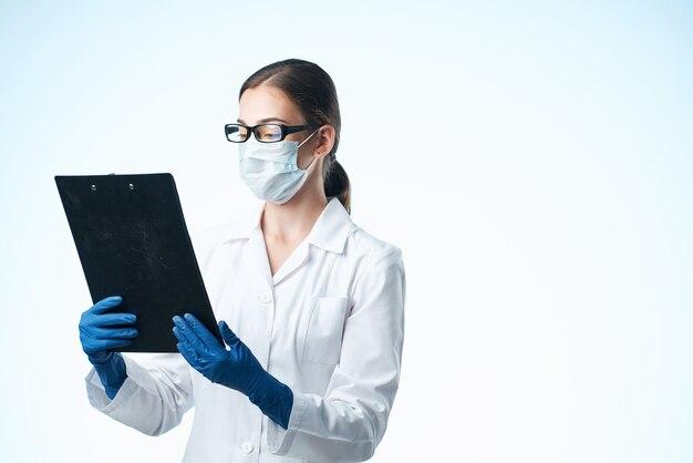 Vrouwelijke arts in witte jas medisch masker documenteert laboratorium