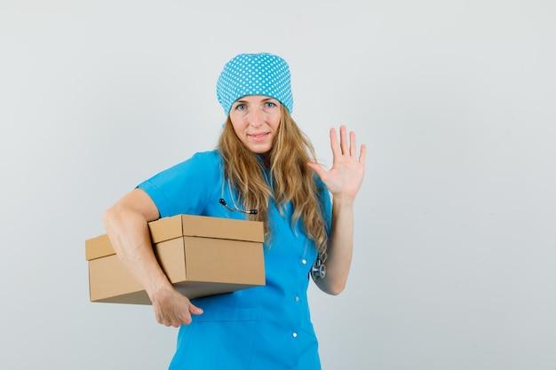 Vrouwelijke arts kartonnen doos houden, zwaaiende hand in blauw uniform en op zoek vrolijk.