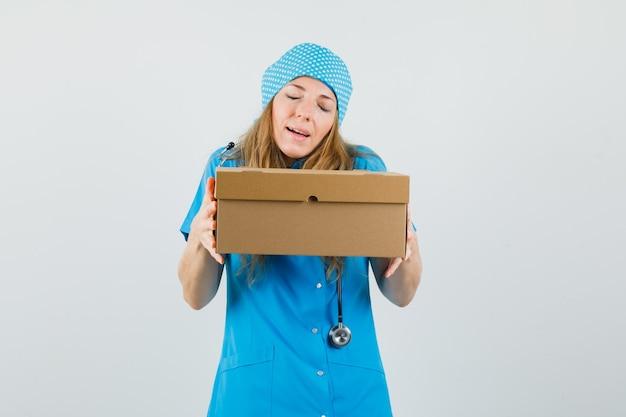 Vrouwelijke arts kartonnen doos in blauw uniform houden en vredig kijken.