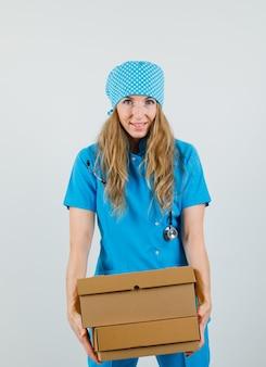 Vrouwelijke arts kartonnen dozen in blauw uniform houden en op zoek vrolijk
