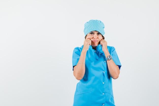 Vrouwelijke arts knijpt in haar wangen in blauw uniform en ziet er somber uit