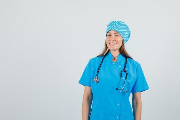 Vrouwelijke arts knipperend oog en lachend in blauw uniform