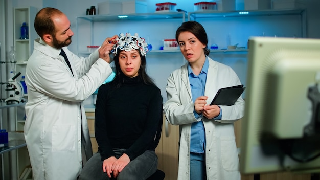 Vrouwelijke arts legt tomografiescan uit vanaf monitorcomputer terwijl man-onderzoeker eeg-headset aanpast die hersenreacties controleert