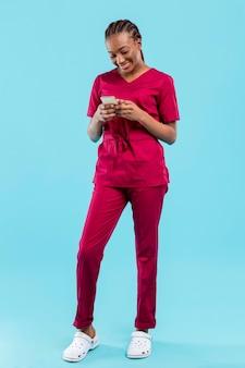 Vrouwelijke arts met behulp van de telefoon naast blauwe muur
