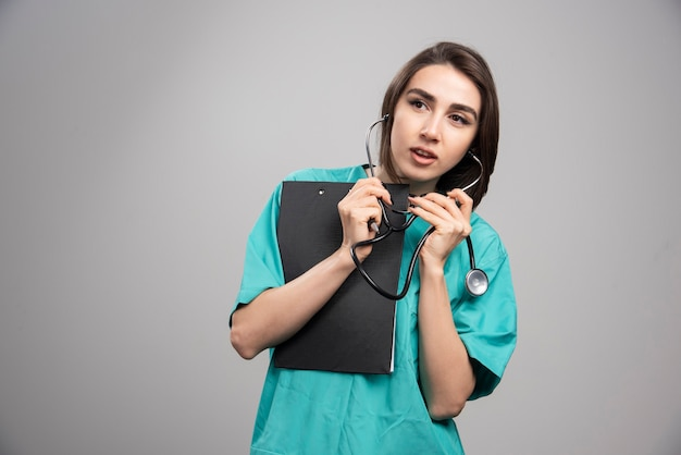 Vrouwelijke arts met behulp van een stethoscoop op een grijze achtergrond. hoge kwaliteit foto