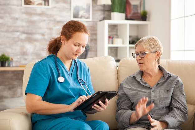 Vrouwelijke arts met behulp van tablet pc en senior vrouw in verpleeghuis.