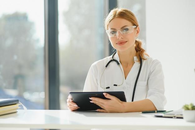 Vrouwelijke arts met behulp van tabletcomputer in het ziekenhuis