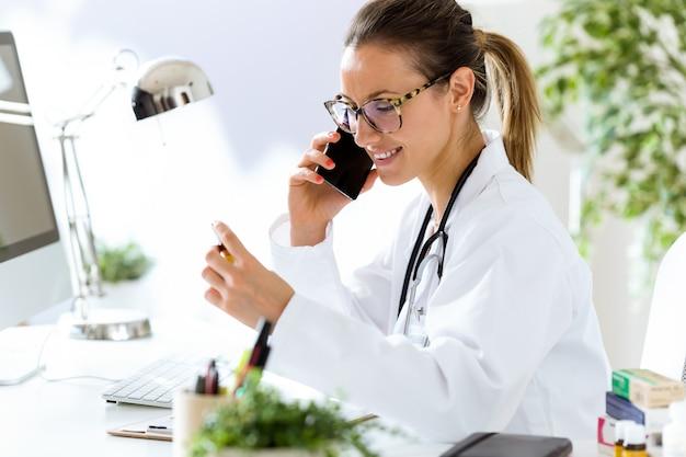 Vrouwelijke arts met behulp van zijn mobiele telefoon in het kantoor.