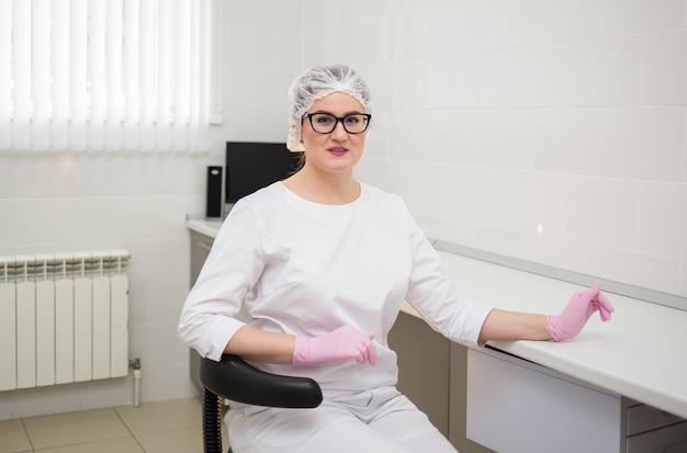 Vrouwelijke arts met een bril en een wit uniform zit aan een bureau in het kantoor met roze wegwerphandschoenen en een pet
