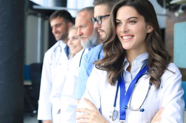 Vrouwelijke arts met een groep gelukkige succesvolle collega's.