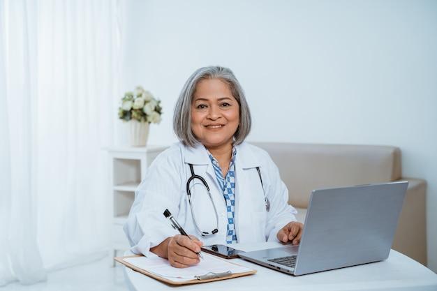 Vrouwelijke arts met een laptop op de tafel