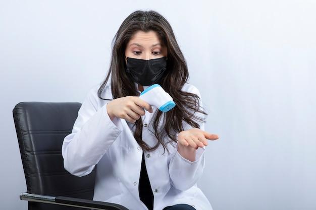 Vrouwelijke arts met een medisch masker die de temperatuur op de witte muur controleert.