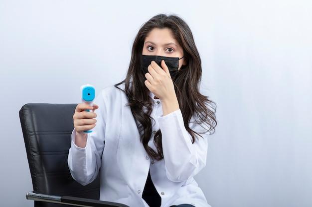 Vrouwelijke arts met een medisch masker die een thermometer vasthoudt en naar de voorkant kijkt.