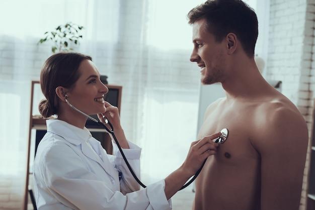 Vrouwelijke arts met een stethoscoop in kantoor. arts luistert naar hartslag met stethoscoop.