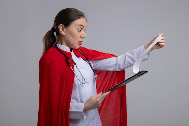 Vrouwelijke arts met een stethoscoop in wit medisch uniform en rode superheld cape met klembord met blanco pagina's kijken verbaasd staande over witte muur