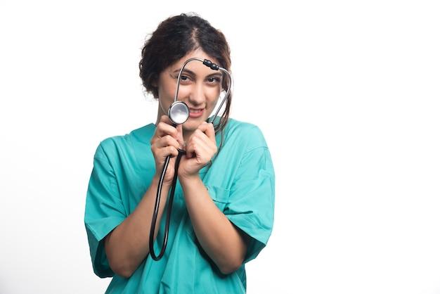 Vrouwelijke arts met een stethoscoop op witte achtergrond
