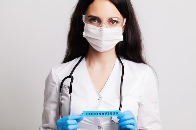 Vrouwelijke arts met inscriptie van het coronavirus