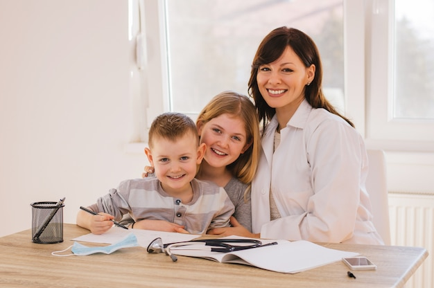 Vrouwelijke arts met kinderen poseren, kijkend naar de camera