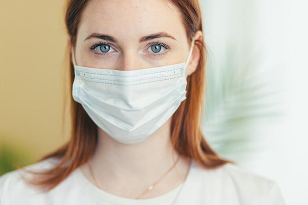 Vrouwelijke arts met medisch masker en toga die naar camera kijkt, close-up foto