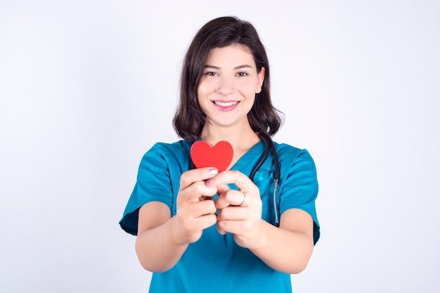 Vrouwelijke arts met rood hart in handen