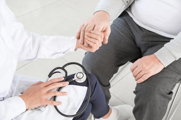 Vrouwelijke arts met senior man die lijdt aan het syndroom van parkinson in kliniek