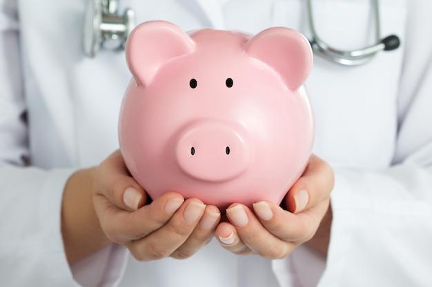 Vrouwelijke arts met spaarvarken. doctor's handen close-up. medische verzekering en gezondheidszorg concept.