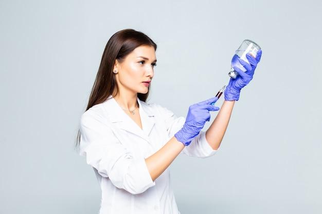 Vrouwelijke arts met spuitvoorbereiding om een inenting te doen die op witte muur wordt geïsoleerd
