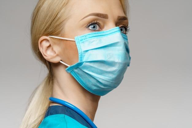 Vrouwelijke arts met stethoscoop die beschermend masker en latexhandschoenen draagt
