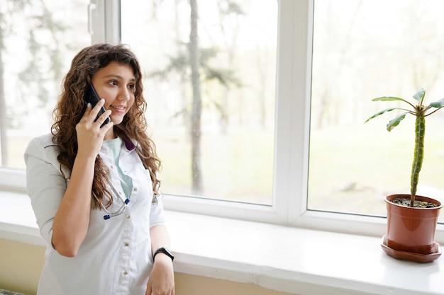 Vrouwelijke arts met stethoscoop die bij mobiele telefoon in kliniek spreekt