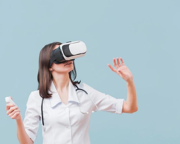 Vrouwelijke arts met stethoscoop die virtuele werkelijkheid ervaren