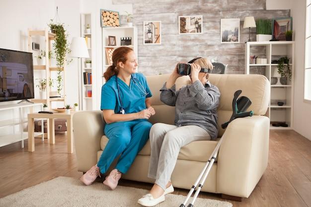 Vrouwelijke arts met stethoscoop en oude vrouw die vr-hoofdtelefoon gebruikt.