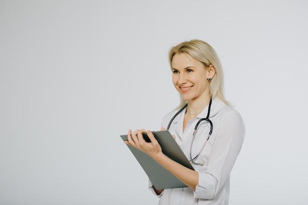 Vrouwelijke arts met stethoscoop het schrijven voorschrift. gezondheidszorg en medisch concept