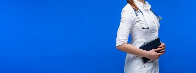 Vrouwelijke arts met stethoscoop op blauwe achtergrond.