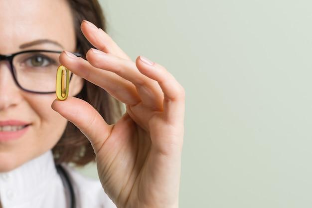 Vrouwelijke arts neemt vitaminecapsule