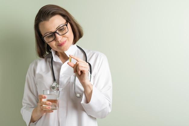 Vrouwelijke arts neemt vitaminecapsule.