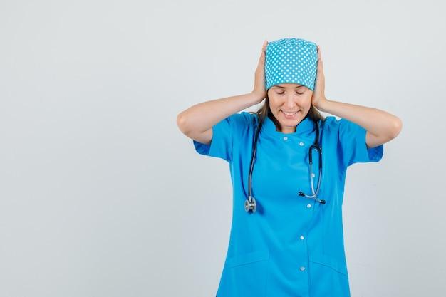 Vrouwelijke arts neerkijkt met de handen op de oren in blauw uniform en kijkt hoopvol. vooraanzicht.