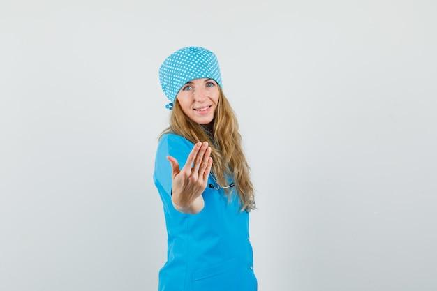 Vrouwelijke arts nodigt uit om in blauw uniform te komen en ziet er vrolijk uit.
